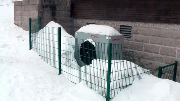 Splitgerät einer Luftwärmepumpe im Winterschnee