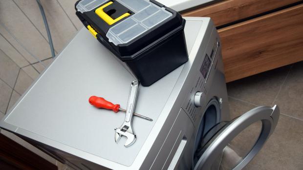 Auf kaputter Waschmaschine liegt Werkzeug bereit