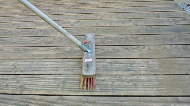 Holzbohlen der Terrasse mit Besen reinigen