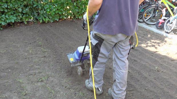 Erdreich wird mit der Gartenfräse aufgelockert