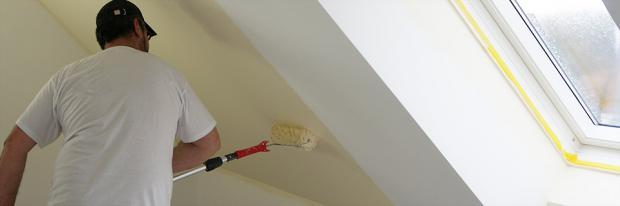 Maler malt die Dachschräge mit der Walze
