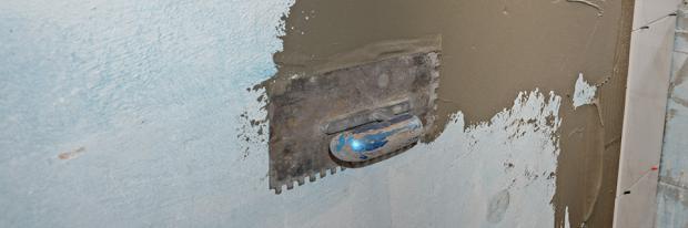 Fliesen legen - Glättspachtel mit Fliesenkleber an der Wand