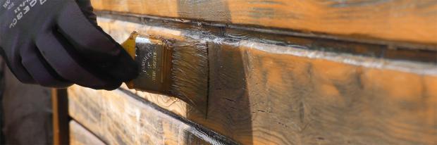 Gartenhaus wird mit dem Pinsel gestrichen – Detailaufnahme