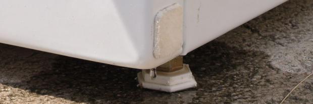 Unter dem Sockel der Waschmaschine steht Wasser