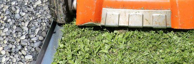 Rasenmäher fährt an Rasenkante aus Metall entlang