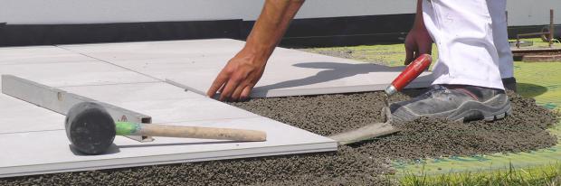 Terrassenplatte wird in den Drainagebeton gelegt
