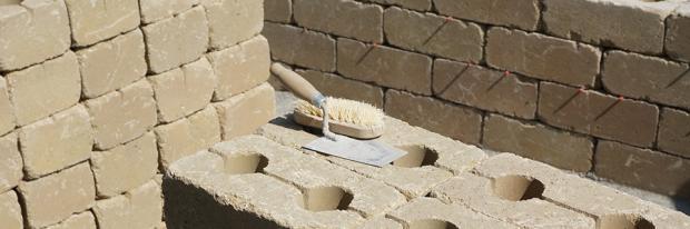 Betonsteine mit Maurerkelle beim Gartenmauer selber bauen